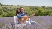 Passionate multiethnic couple playing guitar serenading in lavender field on summer vacations. Loving charming woman embracing african american man from behind while guy playing guitar and singing.