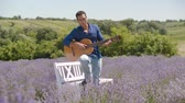 Positive carefree african american man playing acoustic guitar and singing along in lavender field during summer vacations. Joyful multi ethnic guy with guitar relaxing in blooming floral glade.
