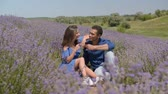 kırmızı şarap : Cheerful multiethnic couple toasting with red wine in blooming lavender field during romatic date. Positive loving diverse couple with red wine enjoying closeness on summer vacations in countryside.