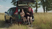 karty do gry : Excited carefree multiethnic women having fun playing cards in car trunk while enjoying summer vacations road trip. Beautiful hipster female friends relaxing in countryside while travelling by car.