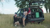 irritação : Upset female travelers checking out flat tyre on car during summer vacations road trip. Annoyed women puzzled about punctured tire, expressing disappointment and hopeless while traveling on rural road Vídeos