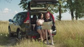 Positive multiethnic young women reading travel map sitting in car trunk, searching location during summer vacations road trip. Cheerful girlfriends travelling by car using paper map to navigate.