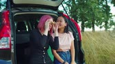 jumelles : Positive multiracial young women travelers sitting in car trunk, looking through binoculars at scenic view, enjoying landscape and talking while travelling by car in countryside on summer vacations.