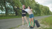 дорожный знак : Cheerful multiracial young female travelers with suitcases hitchhiking with a cardboard sign on roadside. Joyful stylish women hitchhikers catching a ride on rural road during summer vacations travel.