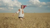 Carefree positive young female in stylish clothes spinning around in golden wheat field during beautiful sunset, feeling happiness, freedom and joy, looking with alluring modest smile in summertime. Stockvideo