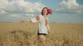 Graceful charming pink-haired young woman in ukrainian national clothes with hair fluttering in the wind having fun, whirling in golden wheat field, rejoicing freedom and leisure at sunset. Stockvideo