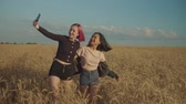 Excited positive multiethnic women taking selfie on smart phone in wheat field at sunset. Cheerful carefree females posing for selfie shot, making funny faces and fooling around on summer vacations. Stockvideo