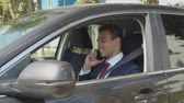 au volant : Positive attractive confident african american businessman talking on cellphone with business partners while sitting in car. Successful black entrepreneur making a phone call while driving vehicle.