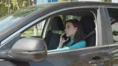 au volant : Lovely brunette female driver chatting on cellphone and checking the time on wristwatch while stuck in traffic jam. Beautiful woman having conversation on mobile phone while driving car in traffic jam
