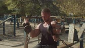 kıvırmak : Muscular built handsome athlete working out at outdoor gym, sitting on weight training bench and doing bicep curls in seated position with two heavy dumbbells during sport training on fresh air. Stok Video