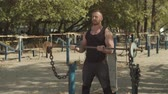 kıvırmak : Determined muscular fit man training with barbell, doing biceps curls for chest muscle during outdoor workout. Handsome bodybuilder doing heavy weight exercise for biceps with barbell at outdoor gym.