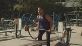buikspieren : Brutal muscular bodybuilder doing heavy deadlift exercise at outdoor gym. Concentrated athletic fit man pumping up muscles with barbell, practicing upright row weight training during outdoor workout.