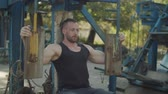 sportovní výstroj : Motivated muscular fit man flexing muscles on chest press machine during outdoor workout. Bodybuilder doing strength training exercises and working out with seated chest press machine outdoors.