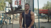 sportos : Confident strong muscular built man doing pushdown on cable machine in outdoor gym. Athletic fit handsome bodybuilder exercising triceps pushdown at the rope cable machine during outdoor workout.