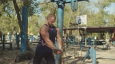 buikspieren : Brutal handsome bodybuilder working out training in outdoor gym, gaining weight pumping up muscles on his chest with cable crossover. Muscular strong man doing exercise on cable crossover outdoors. Stockvideo