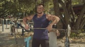 buikspieren : Muscular male bodybuilder working out in outdoor gym doing exercises with barbell. Athletic fit man performing upright -row weigth training exercise, lifting barbell straight up to collarbone outdoors