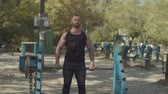 motivatie : Confident motivated bodybuilder doing powerlifting training with barbell in outdoor gym. Muscular athlete with perfect fit shoulders, biceps and triceps lifting barbell during weight training outdoors