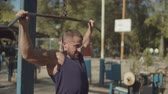 sportovní výstroj : Confident determined male bodybuilder performing lat pulldown weight exercise with wide grip overhand in outdoor gym. Concentrated fit man practicing upper body strength exercise for upper back.