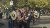 kıvırmak : Handsome concentrated strong fit man performing barbell biceps curls while sitting on bench in outdoor gym. Determined muscular bodybuilder training and pumping up biceps with barbell outdoors.