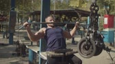 sportovní výstroj : Handsome male bodybuilder doing strength training exercise using cable lat pulldown machine during outdoor workout. Determined strong fit man flexing muscles, performing shoulder pulldown exercise.