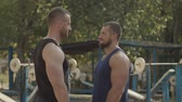 enemy : Two determined rival bodybuilders with perfect trained muscular bodies facing each other outdoors. Serious motivated athletic fit men making duel by a look while meeting before outdoor workout.