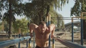 sportovní výstroj : Shirtless determined athletic fit man with well trained body doing triceps dips on parallel bars in outdoor gym. Muscular bodybuilder working out arms, training triceps on dips horizontal bars. Dostupné videozáznamy