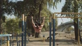 sportovní výstroj : Shirtless motivated strong athlete with perfect trained body doing gymnastic exercises on crossbar while working out in outdoor gym at sunset. Muscular man training doing backflip on horizontal bar. Dostupné videozáznamy