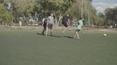 hitting : Street soccer player kicking a ball in attempt to score a goal during football game in the pitch. Motivated offensive footballer taking a shot on target while playing soccer match on sports field. Stock Footage