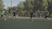 hitting : Positive street football players playing soccer game on the pitch in neighbourhood. Offensive team attacking opponent goal, striker taking a shot on goal and football goalie making a save during match