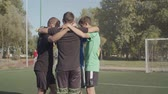 espíritos : Concentrated street soccer team with ball standing in circle and embracing on the pitch before football game. United football players in huddle encouraging for winning soccer match on sports field. Stock Footage