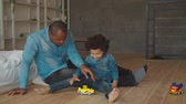 zoon : Affectionate handsome african father and adorable preschool mixed race son playing with colorful car toys on the floor in domestic room. Positive family with child having fun during weekend at home. Stockvideo