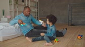 zoon : Positive happy multiethnic family with lovely curly kid having fun, enjoying playtime on the floor in domestic room. Joyful black father and little mixed race son playing with colorful toys at home.