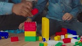 zoon : Close-up of african child and fathers hands building tower from colorful plastic construction blocks while sitting on floor in domestic room. African dad developing sons creativity and imagination. Stockvideo