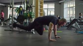 fitness straps : Determined muscular build man training abs core body muscles using TRX bands in health club. Sporty fit bodybuilder exercising abdominals on suspension straps during total body workout at modern gym. Stock Footage