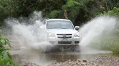 wyscigi : Small 4x4 truck drives around corner into two puddles and makes a big splash.