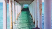 pilíř : A still shot of the turquoise water and the pillars under the boardwalk down at the ocean. Dostupné videozáznamy