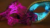 роль : Dolly shot of two party or celebration masks one blue and one pink sitting on a wooden table. Стоковые видеозаписи