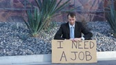 necessidade : Businessman Sitting Need Job Sign