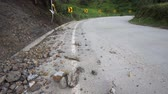 beira da estrada : Tilt up shot of rocks on a road and a broken and crumbled curve in the road warning sign on the side of the road from what appears to be the scene of a motor vehicle accident.