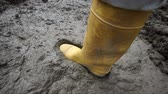 yapışkan : High angle close up shot of an anonymous person wearing a yellow rubber boot stepping into and almost getting stuck in deep and sticky mud. Stok Video