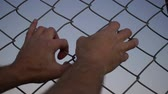 esgrima : Close up evening or dusk shot of the hands of an anonymous male person grabbing a chain link metal wire fence.