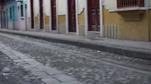 flagstone : Low angle panning shot of a deserted cobblestone and flagstone road in an historic city district with traffic and an anonymous person far off in the background. Stock Footage
