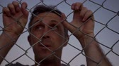 esgrima : Closeup dusk shot of a male person looking through a fence with his hands grabbing the chain link metal wire fence from the opposite or other side of the viewer as if the person were struggling. Vídeos