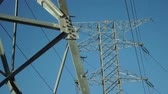 grade : Pulling focus between two high tension electrical pylons used in part of the grid network infrastructure for the distribution and transport of electrical current by the utilities companies. Stock Footage