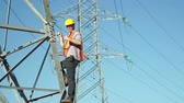 успокоить : Technician in a safety vest and hard hat standing on the side of a high tension electrical tower which is part of the infrastructure for electricity distribution visually inspects the situation and give the viewer a thumbs up gesture.