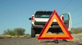 beira da estrada : Broken down truck with hazard lights on and parked on the side of the road and an emergency marker reflective triangle in the foreground. Stock Footage
