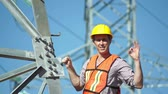 успокоить : Closeup shot of a male technician in a safety vest and hard hat standing on the side of a high tension electrical tower visually inspects the situation and gives the viewer an OK gesture.