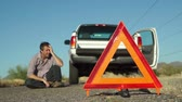 beira da estrada : Male in the distance sits on the roadside with his broken down truck with hazard lights on parked on the side of the road and an emergency marker reflective triangle in the foreground.