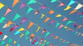 торжества : Panning shot against a clear blue sky background of colorful string pennant triangle flags used for celebrations or grand openings blowing in the wind.