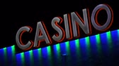 выиграть : Handheld shot of an evening display of a casino sign with color changing LED lights to attract people to come inside and gamble money.